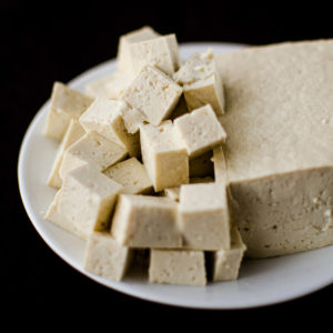 A block of tofu next to tofu cut into cubes on white plate