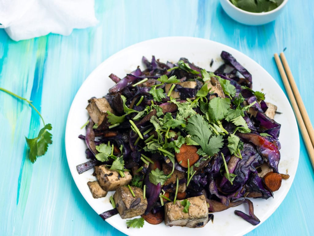 Red cabbage and tofu stir fry on a white plate