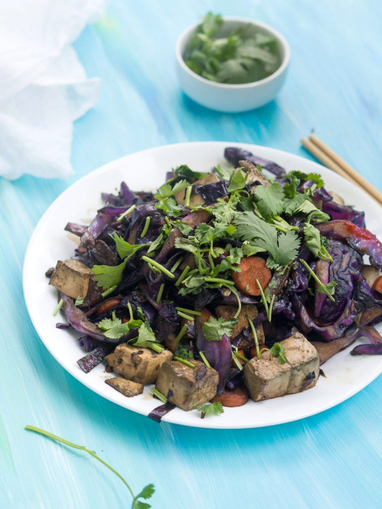 Red cabbage and tofu stir fry on a white plate with chopped green onion