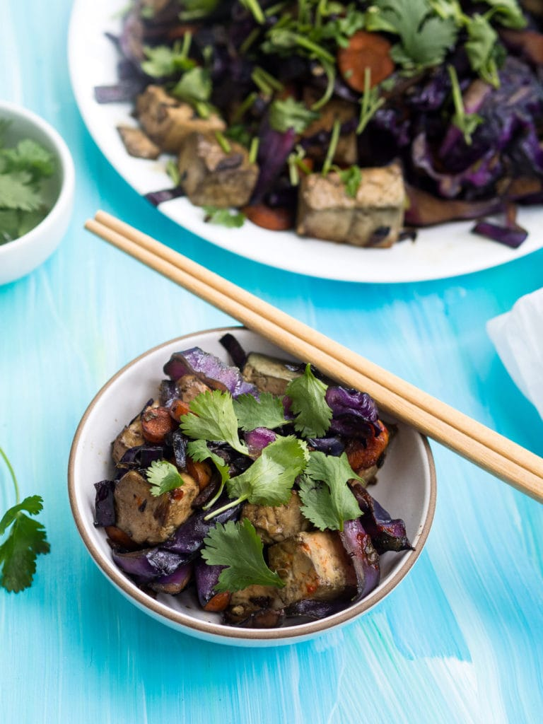Red cabbage and tofu stir fry on a white plate and in a grey bowl