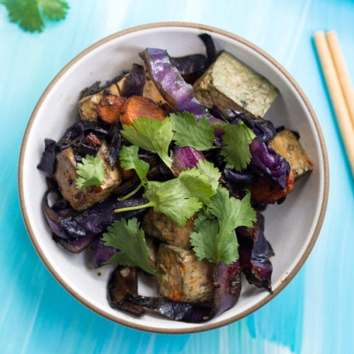 Red cabbage, carrot, mushroom, and tofu stir fry in a white bowl