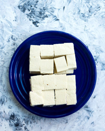 Cubed tofu for red cabbage and tofu stir fry on a blue plate