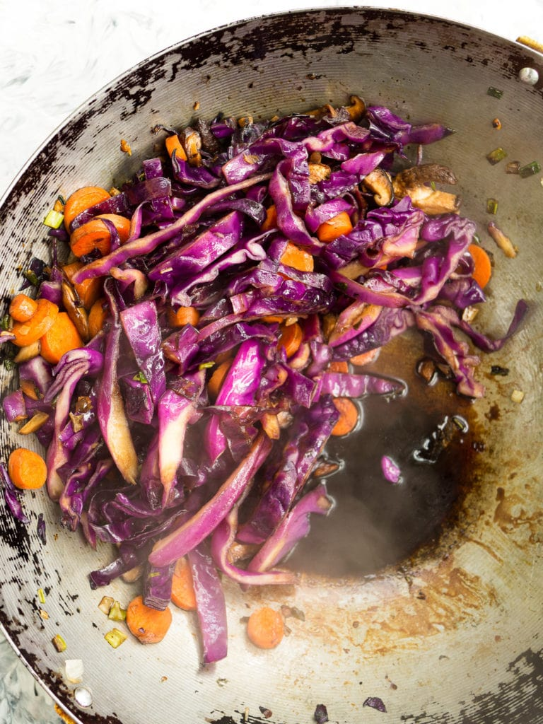 Vegetables and soy sauce in a wok for the red cabbage and tofu stir fry recipe