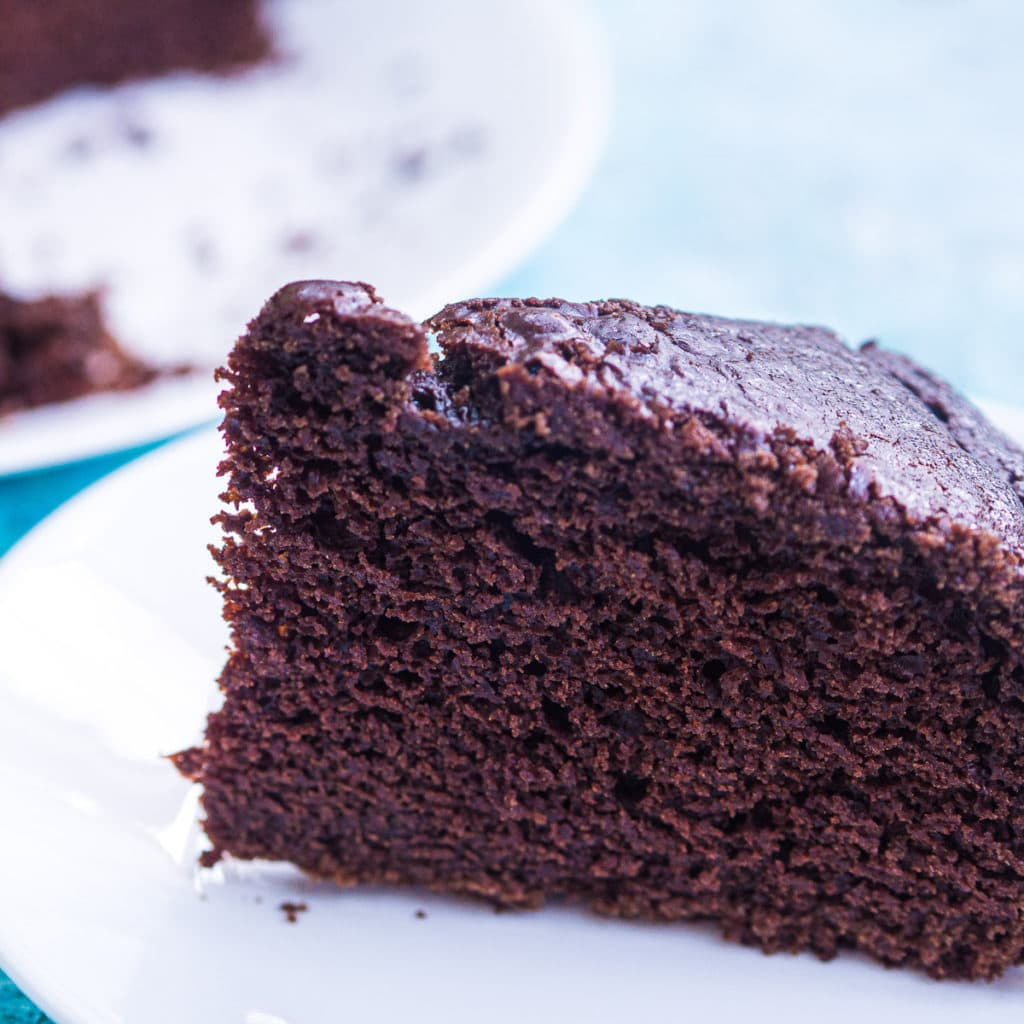 A thick slice of American chocolate cake on a white plate