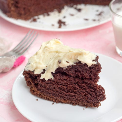 A slice of chocolate cake with cream cheese frosting on a white plate