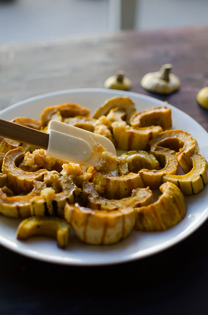 Long view of garlic butter smeared on delicata squash. Recipe from garlicdelight.com.