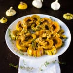 Close up view of delicata squash with garlic butter on white plate with squash ends as garnish. Recipe from garlicdelight.com