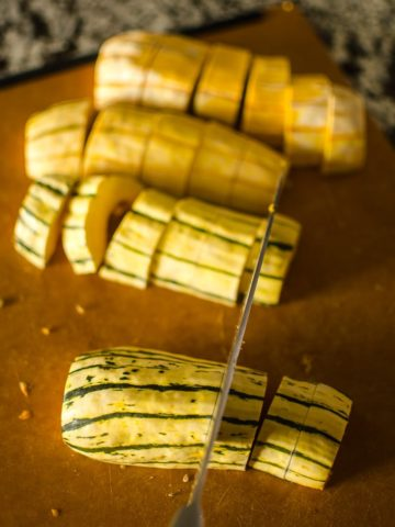 Overhead view of chopping delicata squash. Recipe from garlicdelight.com.