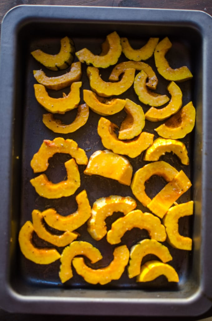 Overhead view of crescent-shaped delicata squash in a baking pan. Recipe from garlicdelight.com.