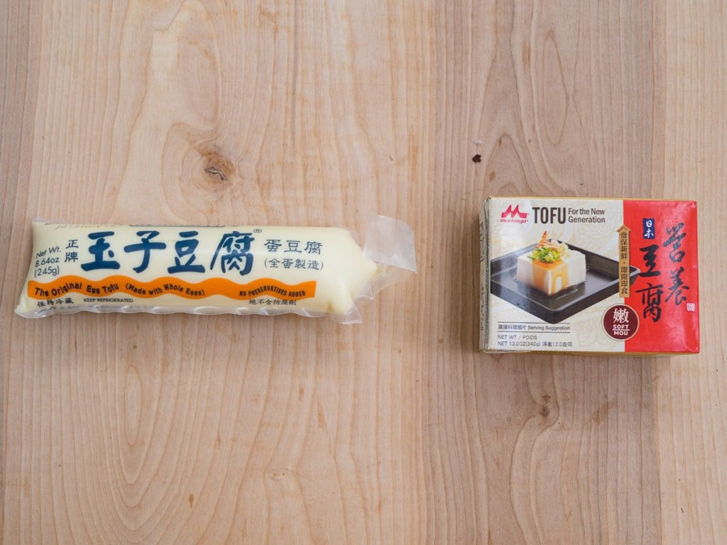 A tube of egg tofu with a box of silken tofu side by side to show a comparison of the different types of tofu