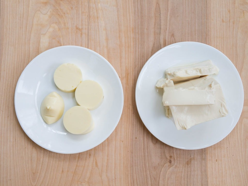 Slices of egg tofu with a block of silken tofu side by side to show a comparison of the different types of tofu