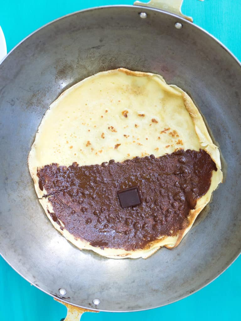 A crêpe reheating in a wok with chocolate