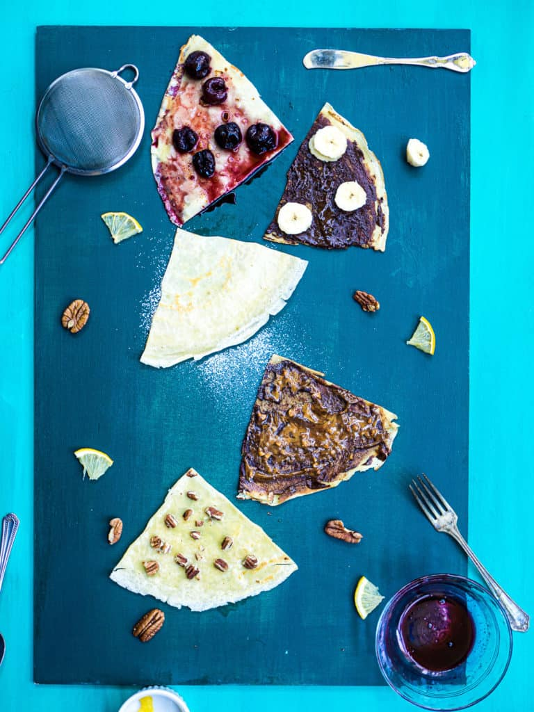 5 different flavored crêpes on a green background with nuts and lemons