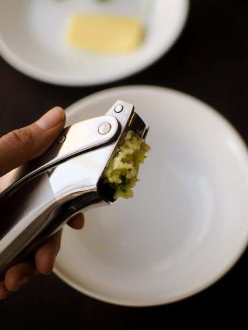 Look at squeezing a garlic clove through a garlic press. Recipe from garlicdelight.com.