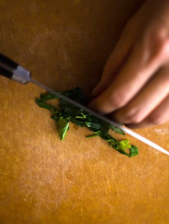 Extreme close up look of Anna chopping cilantro. Recipe from garlicdelight.com.