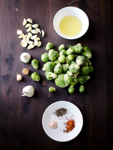 Overhead view of all ingredients for garlic brussels sprouts (salt, pepper, olive oil, brussels sprouts, etc). Recipe from garlicdelight.com.