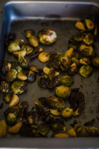 Overhead view of darkly roasted brussels sprouts in baking pans. Recipe from garlicdelight.com.