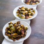 Diagonal front medium shot of roasted brussels sprouts on white plates with white napkin on dark wooden background. Recipe from garlicdelight.com.
