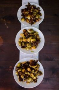 Overhead view of roasted brussels sprouts on white plates with white napkin on dark wooden background. Recipe from garlicdelight.com.