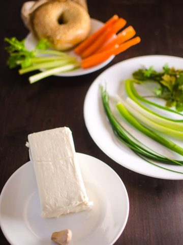 Cream cheese on a plate with herbs in the background as well as a plate of carrot and celery sticks and bagel in the background.