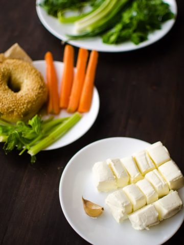 Cubed cream cheese on a plate with herbs in the background as well as a plate of carrot and celery sticks and bagel in the background.
