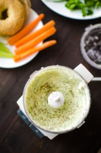 Blended cream cheese with herbs in the food processor bowl with salt & pepper on top.