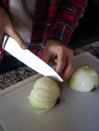 Alex using a chef's knife to thinly slice the onions. Recipe from garlicdelight.com.