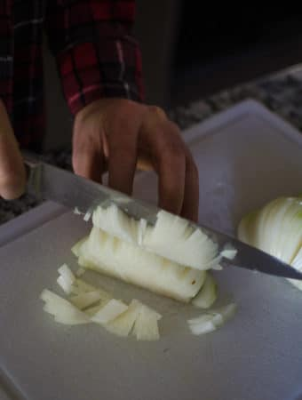 Alex using a chef's knife to finely dice the onions. Recipe from garlicdelight.com.