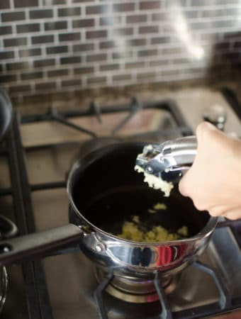View of Anna's hand squeezing garlic through a garlic press directly into the pan. Recipe from garlicdelight.com.