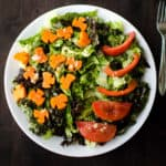 A green salad with sliced carrots, tomatoes, and lettuce with garlic salad dressing on top