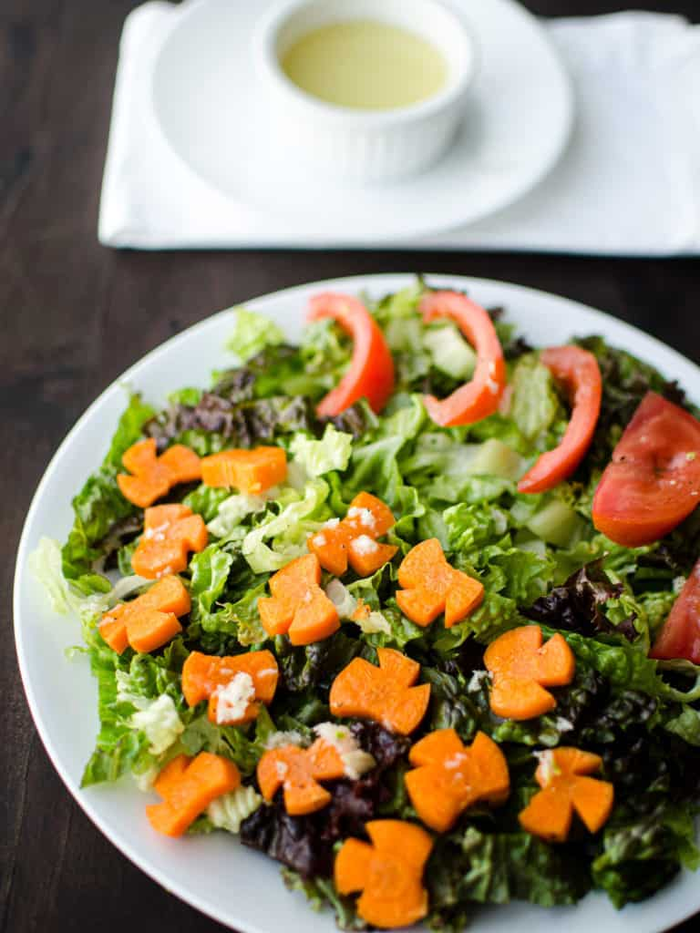 A lettuce salad with sliced carrots and tomatoes with garlic salad dressing on top