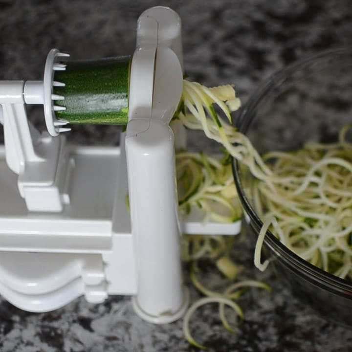Close up look of a spiralizer as it makes zucchini noodles