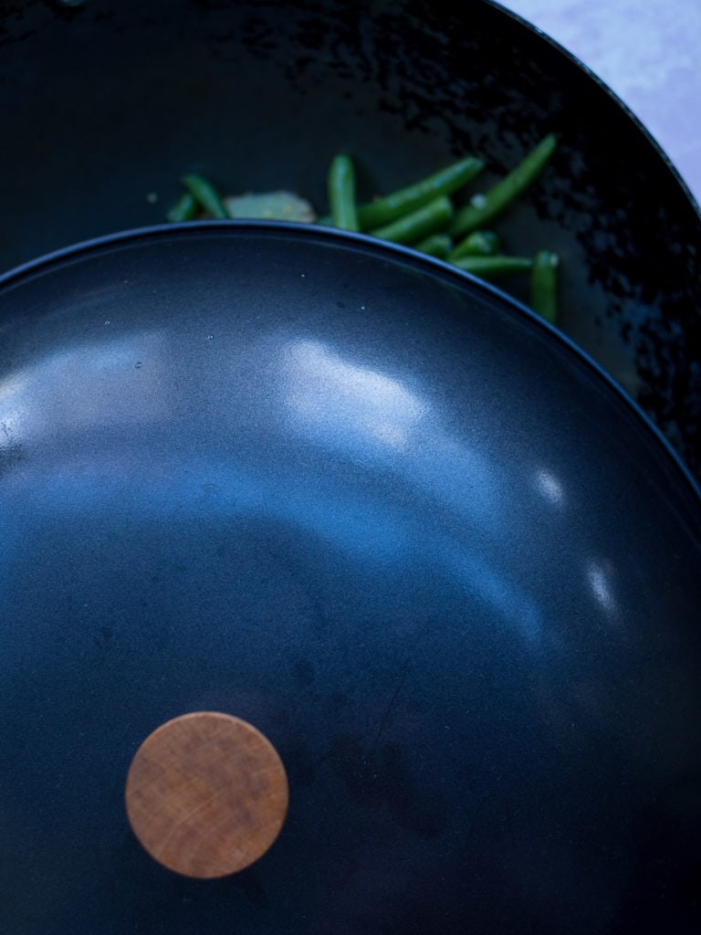 Lid over a wok with green beans