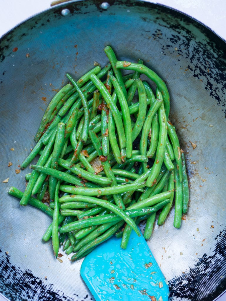 Stir fry of green beans with chili sauce in wok