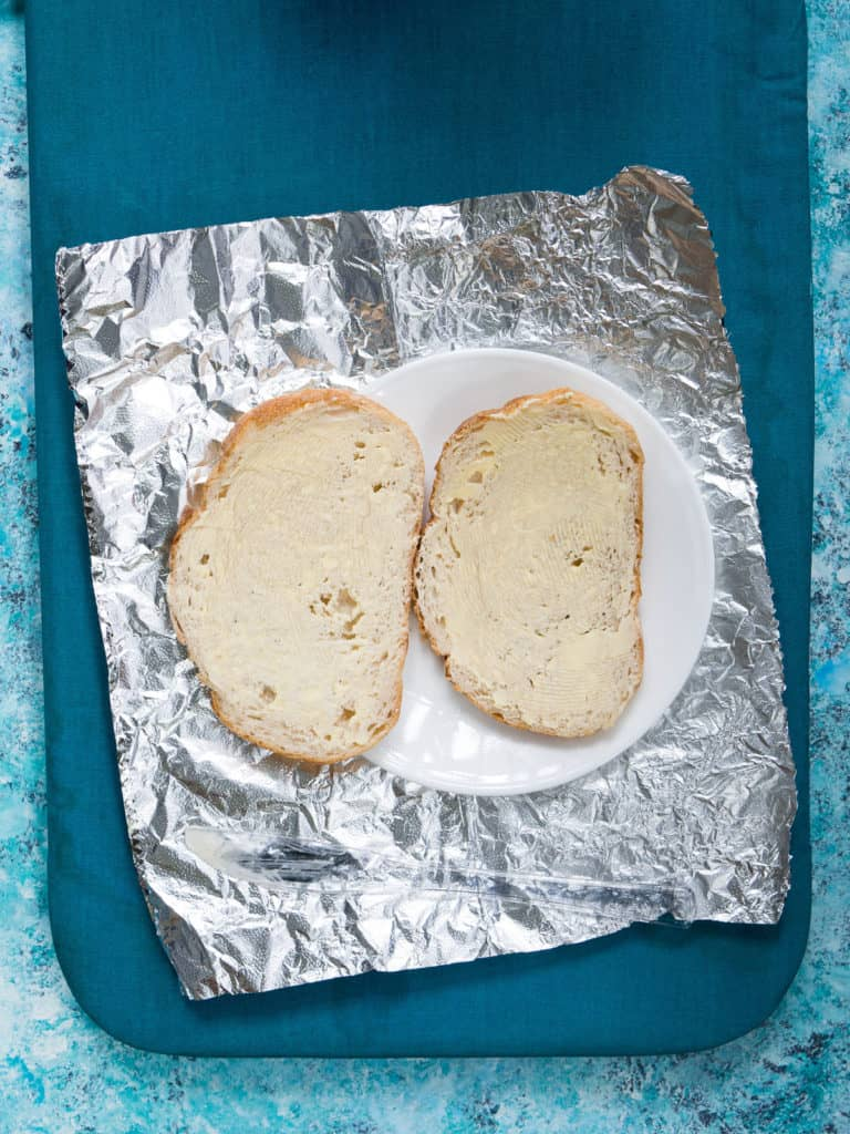 2 slices of buttered bread on a plate on top of tin foil
