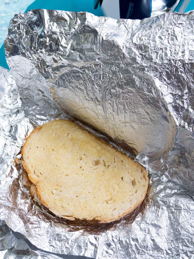 A buttered cheese sandwich wrapped in aluminium foil