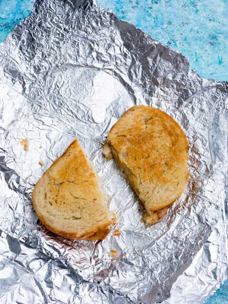 A grilled cheese sandwich cut in half on aluminium foil