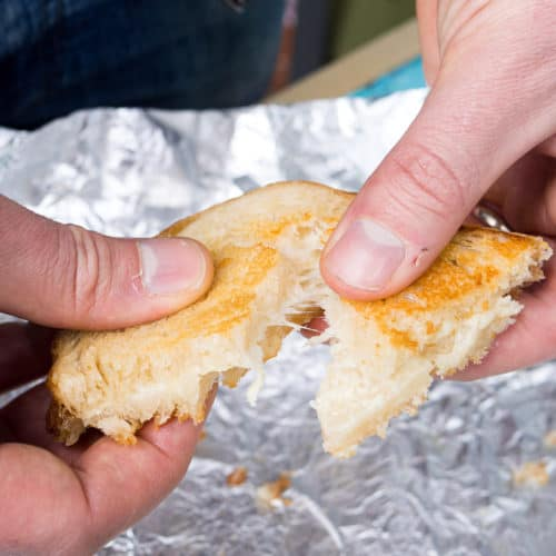 Alex's hands tearing half of a grilled cheese sandwich open