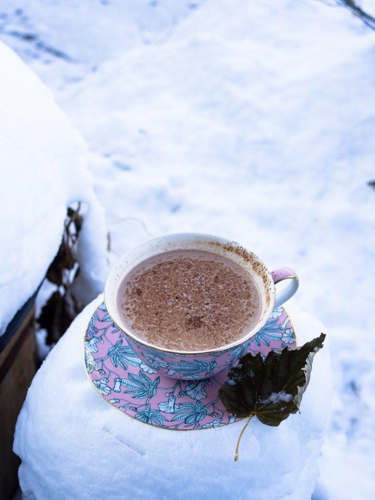 A cup of hot chocolate on a saucer on a table with plenty of snow nearby