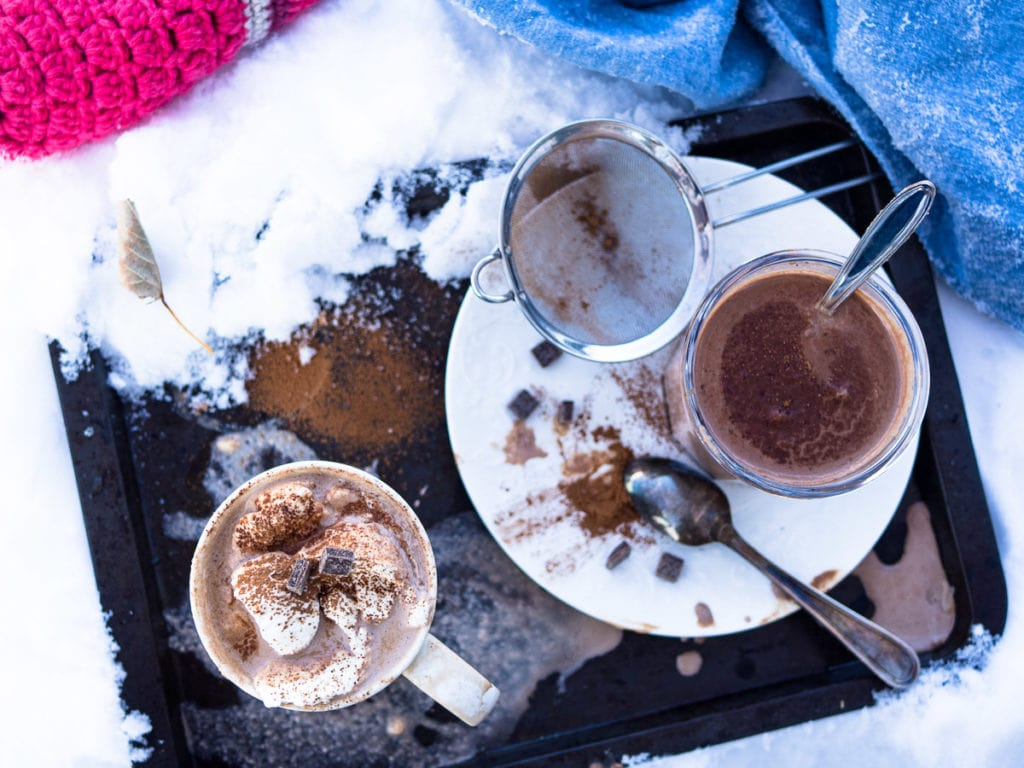 A mug and a glass of hot chocolate with whipped cream on top and a plenty of snow nearby