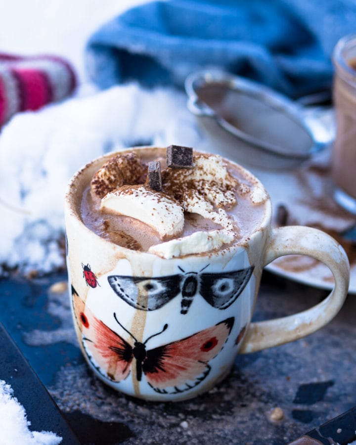 A mug of hot chocolate with whipped cream on top and plenty of snow nearby