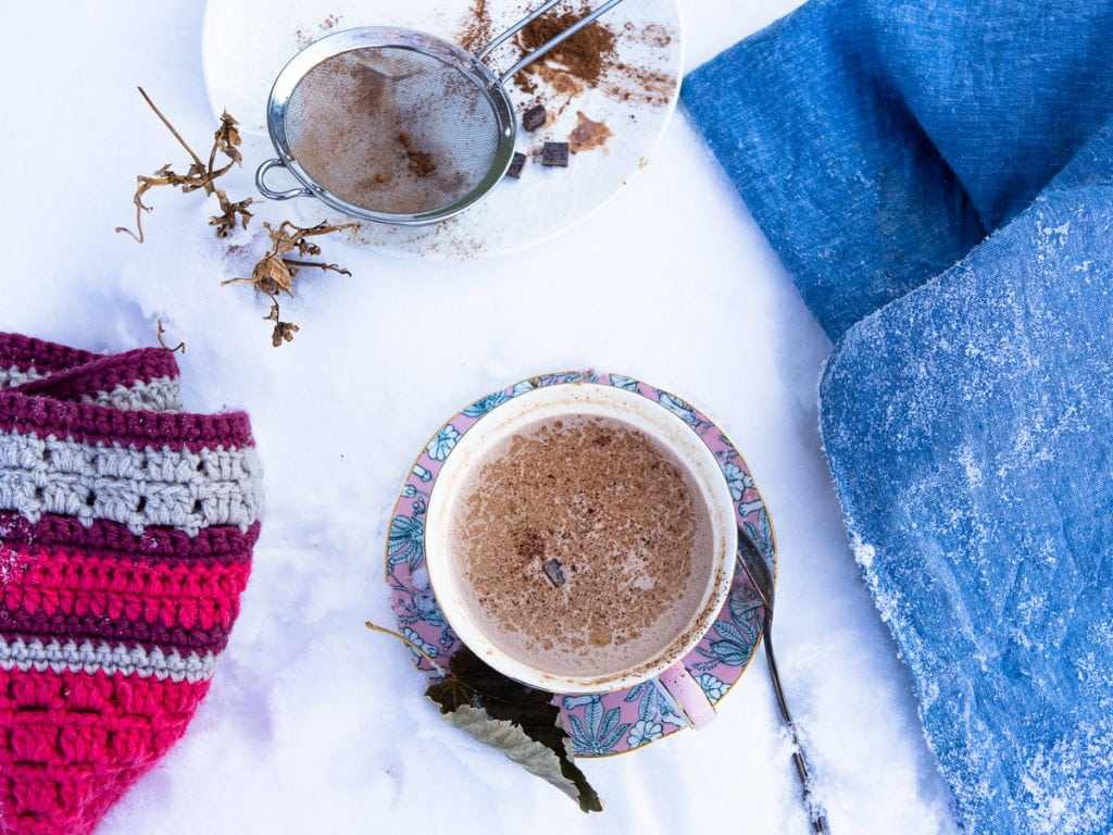 Overhead view of a cup of hot chocolate on a saucer on a table with plenty of snow nearby