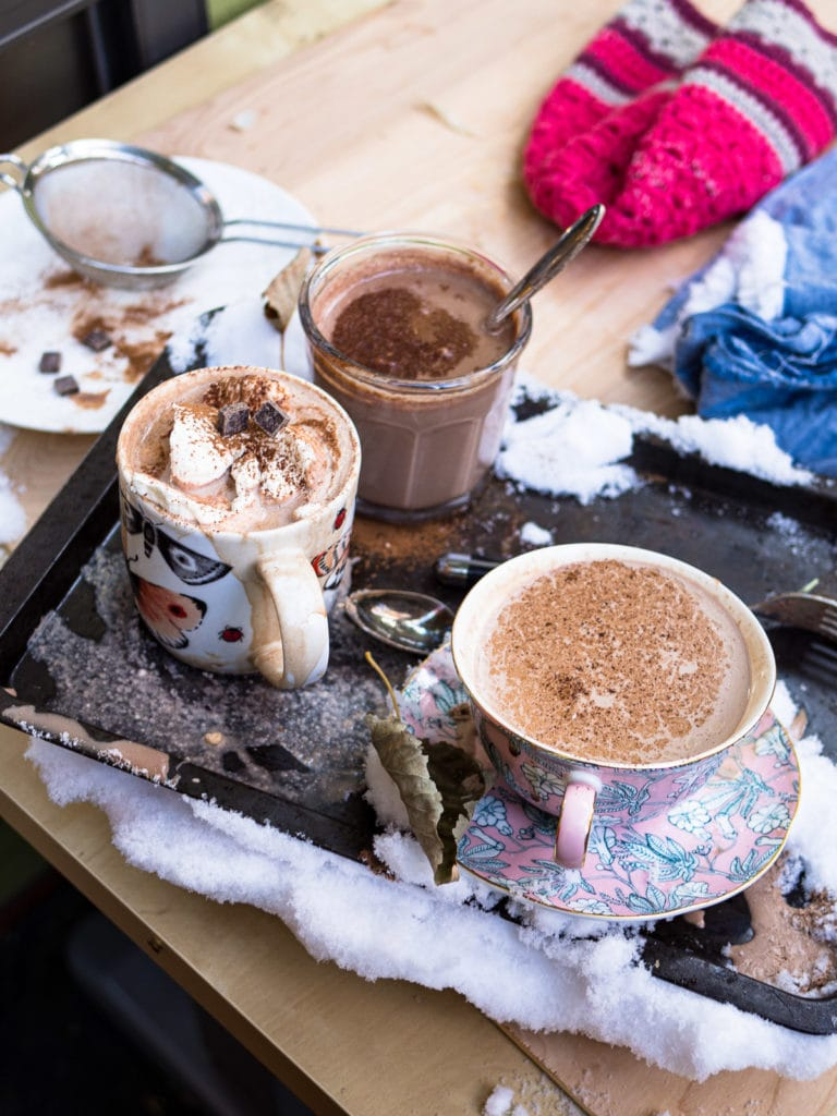A mug, a cup and saucer, and a glass of hot chocolate with whipped cream on a baking tray with snow