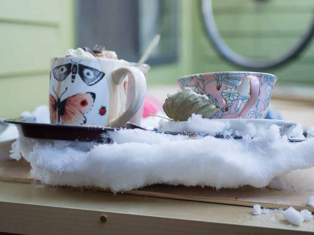 A mug and a cup and saucer with hot chocolate on a baking tray caked with snow