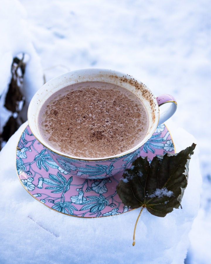 Overhead view of a cup of hot chocolate on a saucer with a leaf and plenty of snow nearby