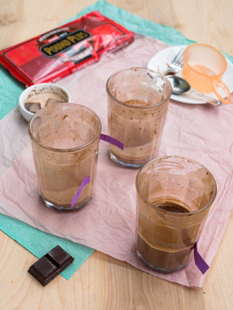 Three tall glasses with different hot chocolate conditions for the hot chocolate vs. hot cocoa taste test
