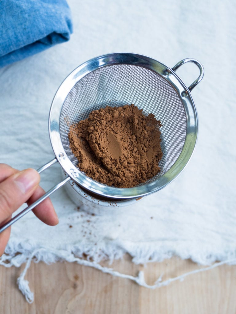 A sieve with cocoa powder sifting into a white mug to show how to break up clumps in hot cocoa