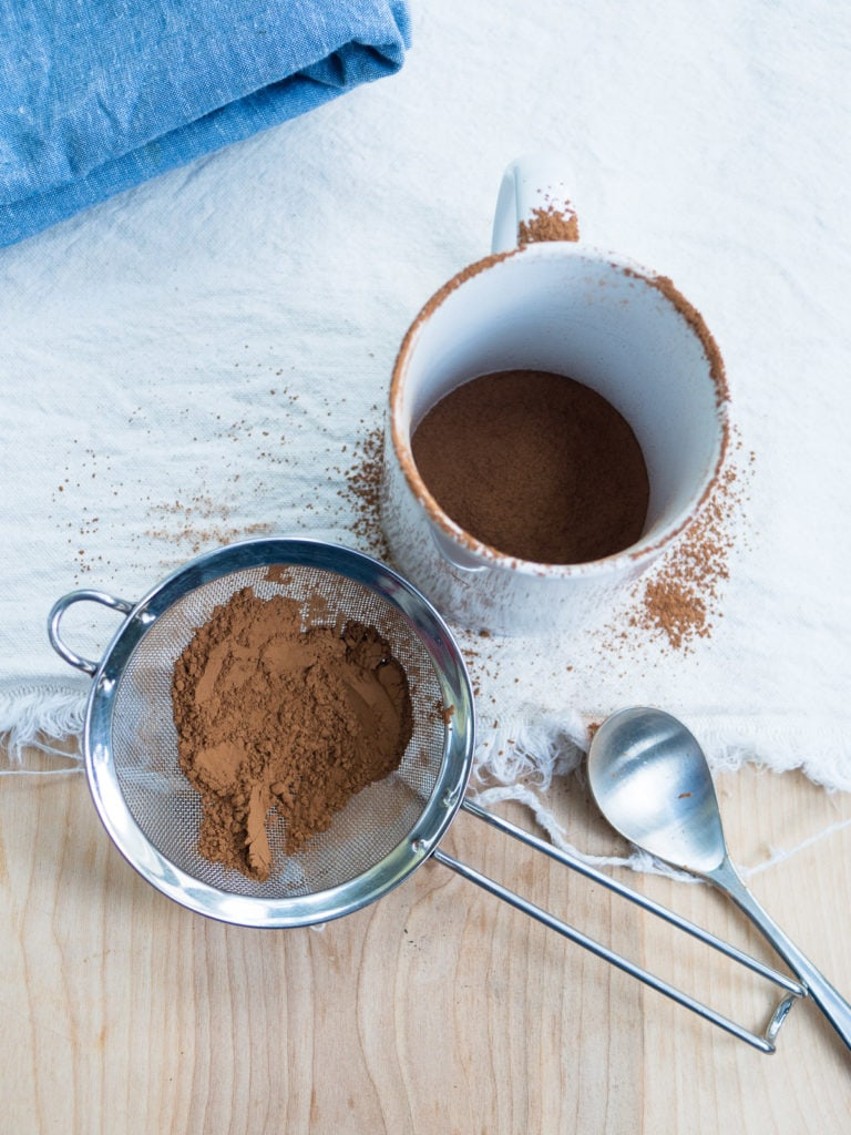 An annotated image of a sieve with cocoa powder next to a white mug to show how messy sifting cocoa powder can be