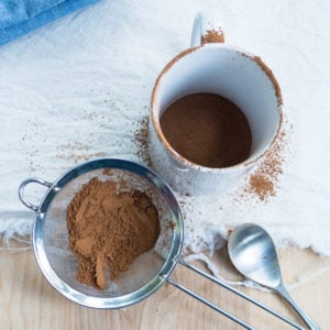 A sieve with cocoa powder and a white mug for the experiment to get rid of clumps from hot cocoa