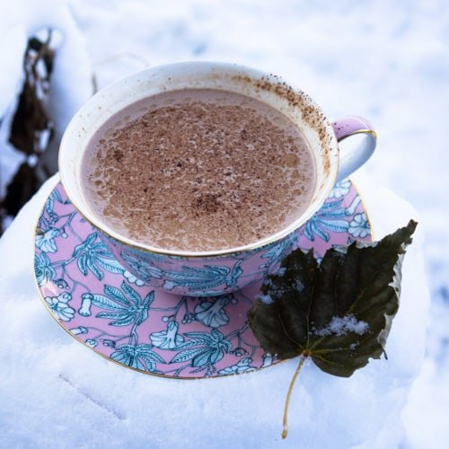 A pink cup of hot chocolate on a matching saucer sitting on top of snow for hot chocolate recipe